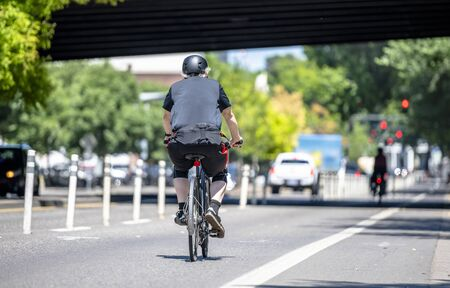 An elderly Man cyclist pedals a bicycle and rides along the Portland down town, preferring like most Portland residents, an active healthy lifestyle and an alternative eco friendly mode of transport