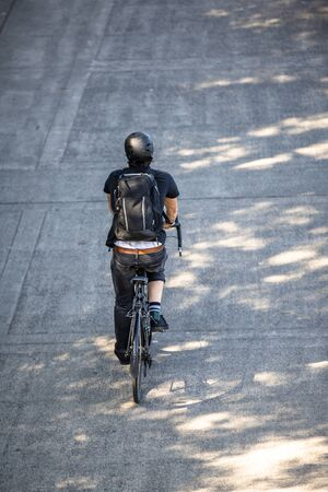 Cyclist in black clothes with a backpack rides a bicycle on a footpath. The use of a bicycle as the main transport for many enthusiasts has grown from a hobby into vital necessity Reklamní fotografie - 129029842