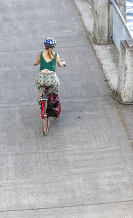 A woman cyclist in sportswear running on the sidewalk on a bicycle, preferring an active way of relaxation, helping her to keep herself in good shape, in a good fit and enjoy life in sunny day