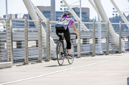 A gorgeous woman cyclist in sportswear and helmet crosses the crossroad on a bicycle, preferring an active way of relaxation, helping her to keep herself in good shape, in a good fit and enjoy life Reklamní fotografie - 129029844
