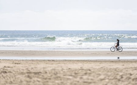Girl cyclist pedals a bicycle and rides along the Pacific Ocean, preferring, an active healthy lifestyle and an alternative eco friendly mode of transport for safe nature environment