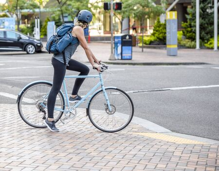 A Woman cyclist pedals a bicycle and rides along the Portland down town, preferring, like most Portland residents, an active healthy lifestyle and an alternative eco friendly mode of transport Reklamní fotografie - 129030536