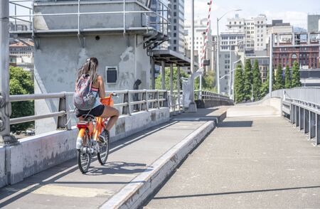 A young girl with her hair and backpack rides an rented orange bike over the bridge and simultaneously flows on the phone, representing the lifestyle of modern youth