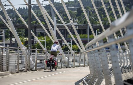 Man Cyclist in sports outfit rides a bicycle on the Tilikum Crossing Bridge. The use of a bicycle as the main transport for many enthusiasts has grown from a hobby into vital necessity Reklamní fotografie - 129030550