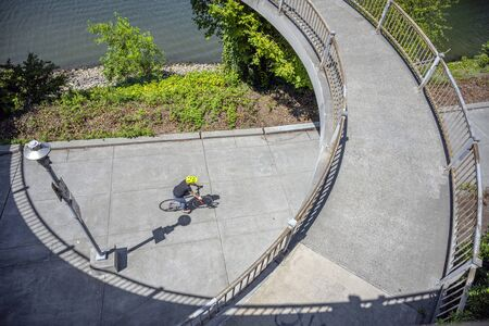 Cyclist rides along a path along a river under an oval bridge. The use of a bicycle as the main transport for many enthusiasts has grown from a hobby into vital necessity Фото со стока