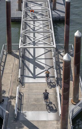 Couple rides a bikes on a bike path crossing a mobile ramp on a floating dock on a river. The use of a bicycle as the main transport for many enthusiasts has grown from a hobby into vital necessity