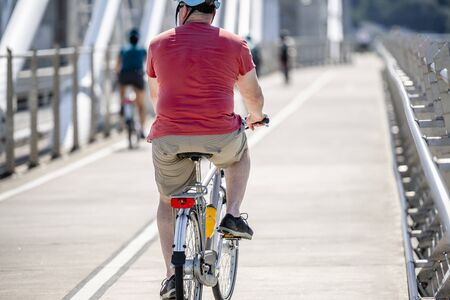 An elderly Man cyclist pedals a bicycle and rides along the Tilikum Crossing Bridge, preferring like most Portland residents an active healthy lifestyle and alternative eco friendly mode of transport Reklamní fotografie - 129030363