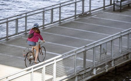 Girl rides a bike on a bike path. The use of a bicycle as the main transport for many enthusiasts has grown from a hobby into a vital necessity for maintaining health and environmental concerns Reklamní fotografie - 129030386
