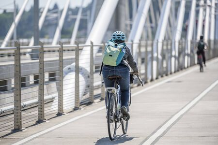 A gorgeous woman cyclist in sportswear and helmet crosses the crossroad on a bicycle, preferring an active way of relaxation, helping her to keep herself in good shape, in a good fit and enjoy life Reklamní fotografie