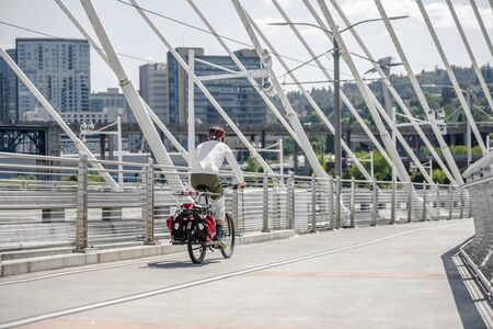 Man Cyclist in sports outfit rides a bicycle on the Tilikum Crossing Bridge. The use of a bicycle as the main transport for many enthusiasts has grown from a hobby into vital necessity Reklamní fotografie - 129030424