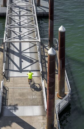 Man rides a bike on a bike path crossing a mobile ramp on a floating dock on a river. The use of a bicycle as the main transport for many enthusiasts has grown from a hobby into vital necessity Reklamní fotografie