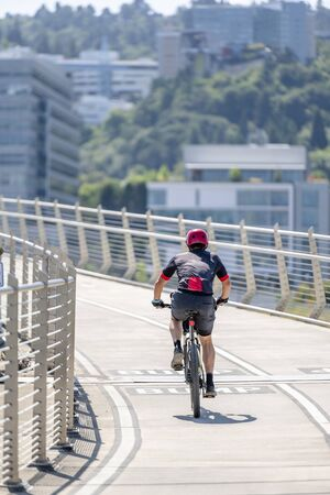 Man Cyclist in sports outfit rides a bicycle on the Tilikum Crossing Bridge. The use of a bicycle as the main transport for many enthusiasts has grown from a hobby into vital necessity