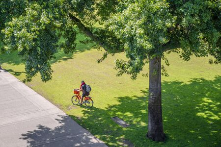 Cyclist with a bicycle resting on the grass in a large meadow of a city park. The use of a bicycle as the main transport for many enthusiasts has grown from a hobby into vital necessity Reklamní fotografie