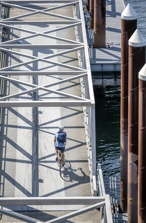 Man rides a bike on a bike path crossing a mobile ramp on a floating dock on a river. The use of a bicycle as the main transport for many enthusiasts has grown from a hobby into vital necessity Reklamní fotografie - 129030451