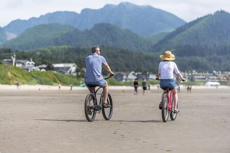 Couple cyclists pedals the bicycles and rides along the Pacific Ocean, preferring, an active healthy lifestyle and an alternative eco friendly mode of transport for safe nature environment Reklamní fotografie - 129030494