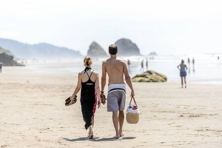 Lovely couple are walking along the shore of the Northwest Pacific Ocean and breathing healthy fresh sea air to strengthen immunity and strengthen the body Standard-Bild - 129030210