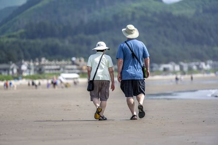 Stocky elderly couple in panamas are walking along the shore of the Northwest Pacific Ocean and breathing healthy fresh sea air to strengthen immunity and strengthen the body Standard-Bild - 129030249