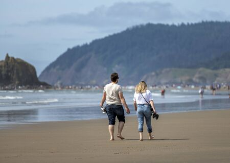 Lovely couple are walking along the shore of the Northwest Pacific Ocean and breathing healthy fresh sea air to strengthen immunity and strengthen the body Foto de archivo