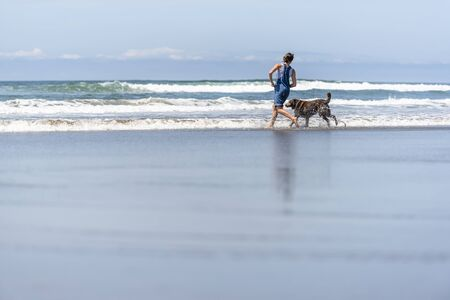 Young girl in denim overalls barefoot running with an old brown Labrador retriever dog along the mirror surface of water of Pacific Ocean in the Northwest enjoying fresh sea breeze Standard-Bild - 129030166