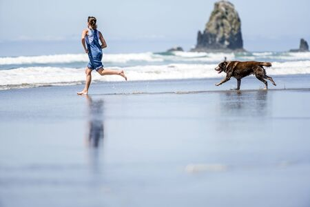 Young girl in denim overalls barefoot running with an old brown Labrador retriever dog along the mirror surface of water of Pacific Ocean in the Northwest enjoying fresh sea breeze Standard-Bild - 129030168