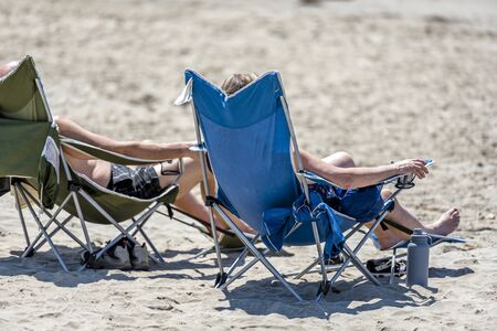 Couple sunbathe on the beach sitting in tourist folding chairs on the shore of the Northwest Pacific Ocean and breathing healthy fresh sea air to strengthen immunity and strengthen the body Standard-Bild - 129030011