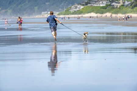 Funny cheerful dynamic man in swimming trunks and t-shirt barefoot running with a playful dog along the mirror surface of water of Pacific Ocean in the Northwest enjoying fresh healthy sea breeze