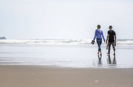 Lovely couple are walking along the shore of the Northwest Pacific Ocean and breathing healthy fresh sea air to strengthen immunity and strengthen the body Standard-Bild - 129030122