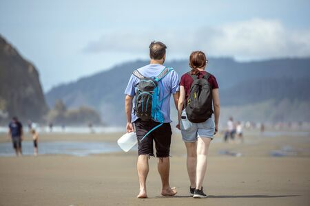 Young couple are walking along the shore of the Northwest Pacific Ocean holding hands and breathing healthy fresh sea air to strengthen immunity and strengthen the body Standard-Bild - 129029948