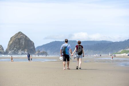 Young couple are walking along the shore of the Northwest Pacific Ocean holding hands and breathing healthy fresh sea air to strengthen immunity and strengthen the body Standard-Bild - 129029951