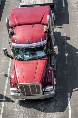 Big rig red powerful professional American bonnet industrial grade semi truck transporting commercial cargo on with flat bed semi trailer running on the wide highway road in sunny day