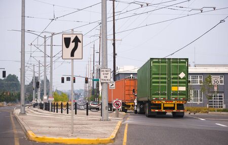 Convoy of professional powerful big rigs semi trucks transporting industrial containers with commercial cargo running on the city street with tram line and buildings