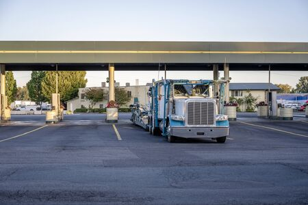 Big rig industrial grade car hauler classic American bonnet semi truck with empty semi trailer stands on the fuel station for refueling and continue to the vehicle loading point for next delivery 스톡 콘텐츠