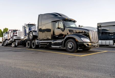 Big rig black powerful semi truck transports new semi trucks tractors coupled one on top of another to form a road train standing on the truck stop parking lot waiting for continued movement