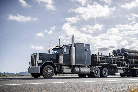 Big rig potente semi camión con capó industrial profesional para entrega de largo recorrido, tuberías de plástico comerciales con semirremolque de bajada en la carretera de verano con árboles de bosque verde a los lados