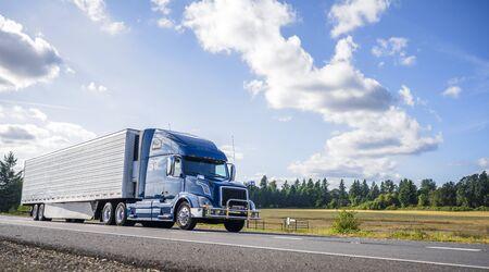 Big rig potente camión semi industrial profesional con capó azul para entrega de carga comercial de larga distancia que va con un semirremolque frigorífico en la carretera de verano con bosques y prados a los lados