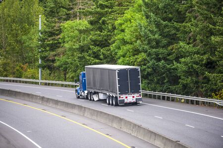Classic American blue bonnet big rig semi truck with sleeping compartment transporting cargo in black covered semi trailer running on the divided highway with green trees on the side 免版税图像 - 129624293