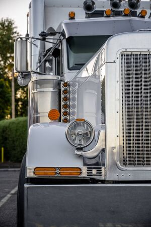 Big rig classic American idol white professional industrial grade semi truck with chrome pipes and horns transporting cargo in semi trailer standing on the truck stop parking lot at twilight time