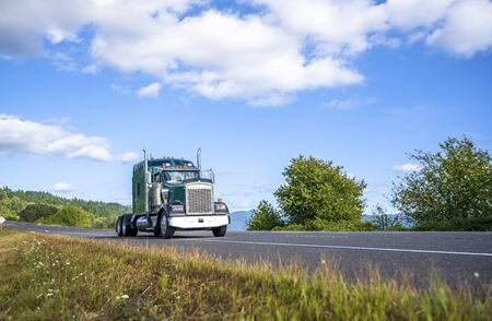 Big rig green American classic bonnet industrial grade semi truck tractor going to warehouse for picking up loaded semi trailer for next delivery running on the road in Columbia Gorge