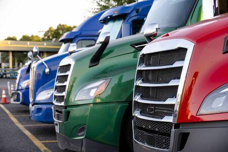 Verschiedene Marken und Modelle Big Rigs Sattelschlepper mit Sattelaufliegern stehen in Reihe auf dem Rastplatz Parkplatz zur Ruhe und halten sich an die Bewegung gemäß dem Zeitplan für eine erfolgreiche Lieferung