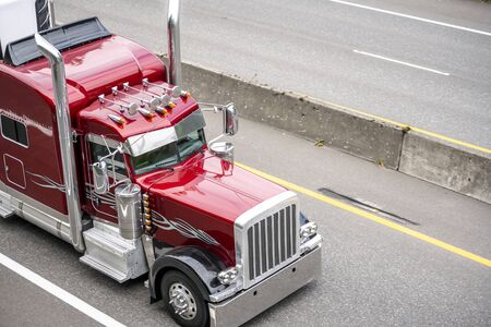 Red big rig classic American bonnet semi truck with high vertical chrome exhaust pipes and visor transporting commercial cargo in refrigerator semi trailer driving on the turning road with trees 版權商用圖片