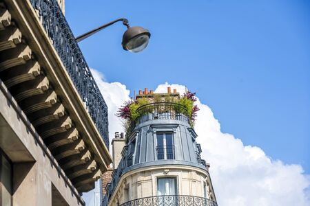 Rounded cone residential apartments multi-storey house with wooden shutters and residential attic and balconies and plants on the roof located on one of the streets of Paris with old buildings