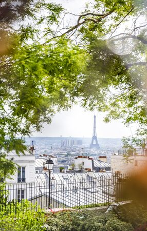Paris cityscape overlooking the target and dream of tourists famous Eiffel Tower and the old city with iron roofs and chimneys from Montmartre hill through the foliage of trees