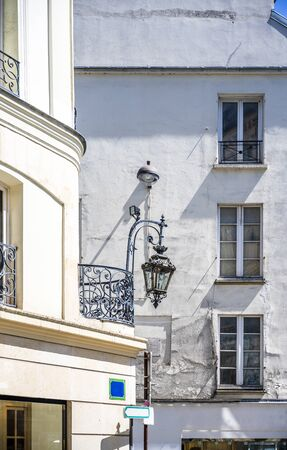 Corner of a street with storey residential building with residential lofts and balconies and business on the ground floor - a classic architectural design of old Paris with an exterior décor