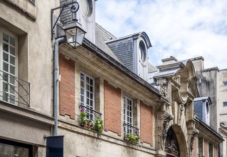 Lantern and stucco decorative elements on the facade of old houses with fancy architecture of the old world- a classic architectural design of old Paris with an intricate exterior decor