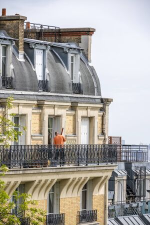 Man repairs his apartment in high-rise brick house with wooden shutters and residential attic and balconies outside the windows located on one of the streets of Paris with old buildings 写真素材