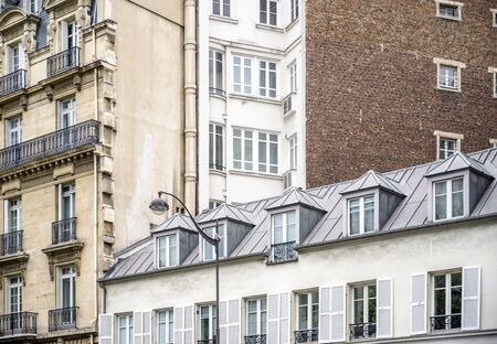 Corner of residential apartments multi-storey house with wooden shutters and residential attic and balconies outside the windows located on one of the streets of Paris with old buildings