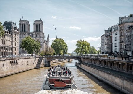 A pleasure boat with tourists on board conducts an excursion tour of the Seine River in the historical Paris area with views of Notre Dame Cathedral and other buildings and sights of the city Stock Photo