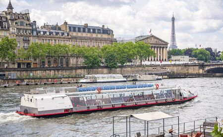 A pleasure boat with tourists on board conducts an excursion tour of the Seine River in the historical Paris area with views of Eiffel Tower and other buildings and sights of the city