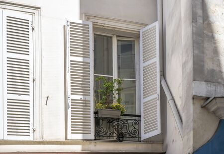 Flowers pot with flowers and plants are exposed outside a window with wooden shutters on fixed metal rims of an impromptu balcony on the facade of a plastered multilevel house
