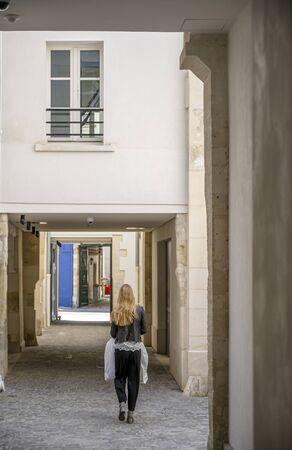 La chica del paquete recorre los patios con edificios de apartamentos de gran altura con pasarelas rectangulares en forma de arco en el viejo París